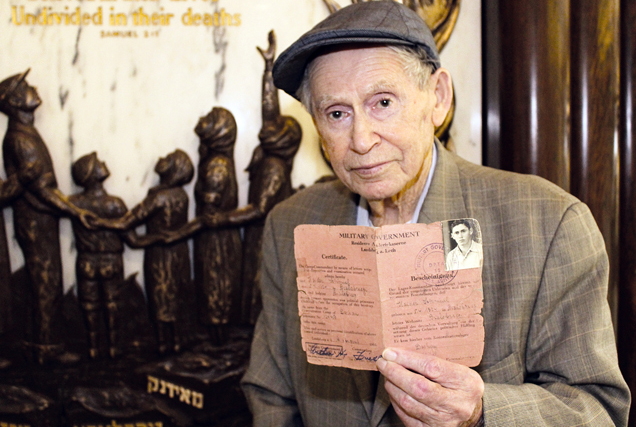 Daytonian Sam Heider in front of the Jewish Federation of Greater Dayton's Holocaust Memorial at the Boonshoft Center for Jewish Culture and Education in Centerville. He holds his identification certificate from Landsberg DP Camp in Germany, where he lived from 1945 to 1949. Photo by Marshall Weiss.