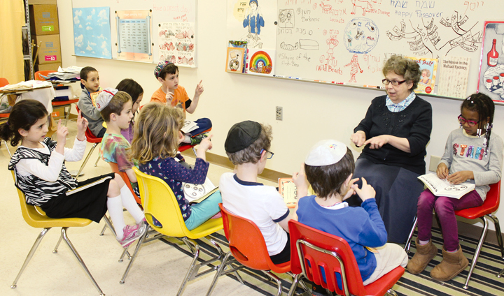 Sandy Sloane-Brenner, Hillel Academy's Judaics teacher for kindergarten through grade 2, reviews the Passover Haggadah with students. Sloane-Brenner has taught at the Jewish day school since 1972.