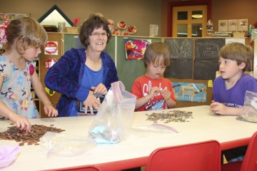 JCC Preschool Supervisor & Lead Teacher Pat Jones and her students count up tzedakah donations brought in by the children, at the Boonshoft CJCE