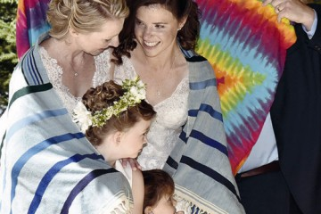 Rabbi David Burstein of Temple Beth Or envelops newlyweds Dr. Melissa Hanna (L) and Dr. Naomi Sandor and their daughters, Julia (L) and Eileen, in his prayer shawls before he offers the Priestly Benediction at their wedding ceremony, Aug. 1 at Benham's Grove in Centerville (Maslov Photography)