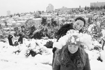 Playing in the snow, with the Jerusalem neighborhood Mishkenot Sha'ananim in the background, Jan. 10, 2013. Photo by Nati Shohat/FLASH90