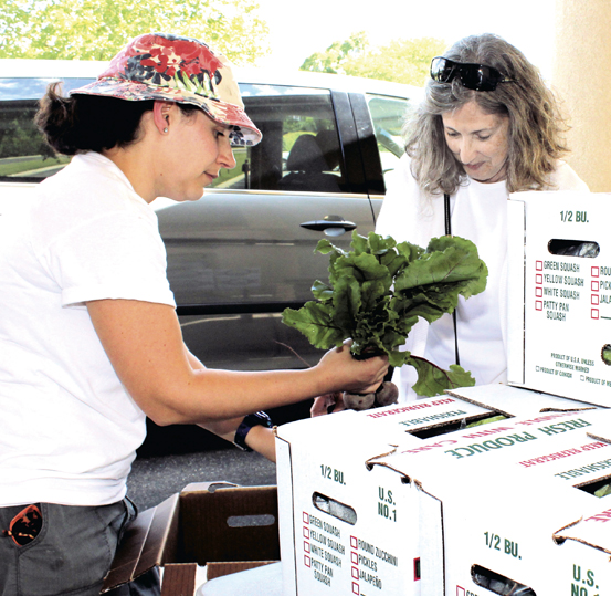 Bev Louis (R) picks up produce from Juliet Glaser, coordinator of the JCC's community supported agriculture project