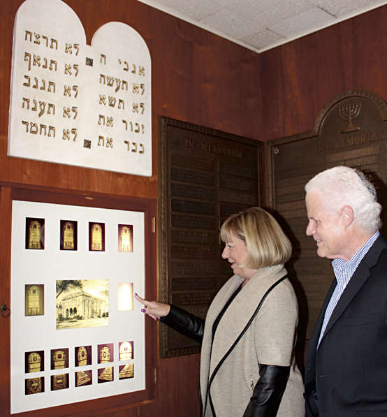 Temple Sholom President Laurie Leventhal and Rabbi Cary Kozberg show archival images from the congregation's previous building, on display in Temple Sholom's Memorial Room. Photo: Marshall Weiss