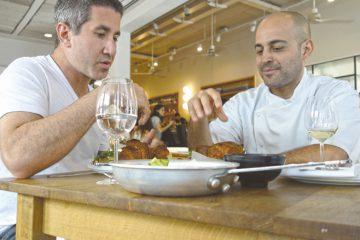 Michael Solomonov (L) tries Meir Adoni's Kubaneh (Yemenite Sabbath Bread) at Mizlala restaurant in Tel Aviv. Photo: Florentine Films