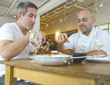 Michael Solomonov (L) tries Meir Adoni's Kubaneh (Yemenite Sabbath Bread) at Mizlala restaurant in Tel Aviv. Photo: Florentine Films