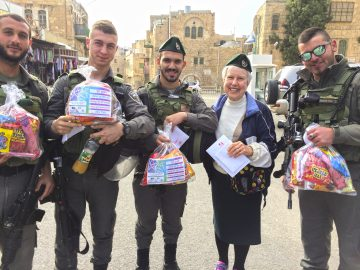 Goldye Kopmar of Dayton gives Purim goodies and letters from Hillel Academy and Beth Abraham students to Israeli soldiers during ZOA's Purim Mission to Israel.
