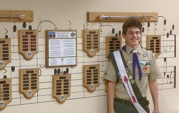 Boy Scout Troop 236's Sam Nicholaisen with the commemorative plaque display he created for his Eagle project, at Oakwood High School