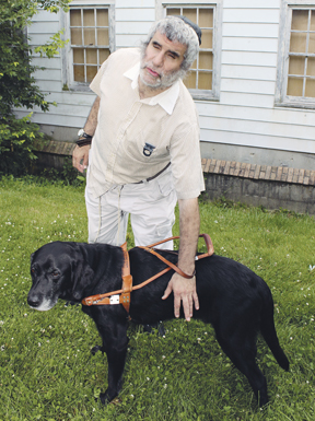 Chaim Segal, shown here with his guide dog, Yahtzee, has completed the first volume of his memoir. Photo: Marshall Weiss.