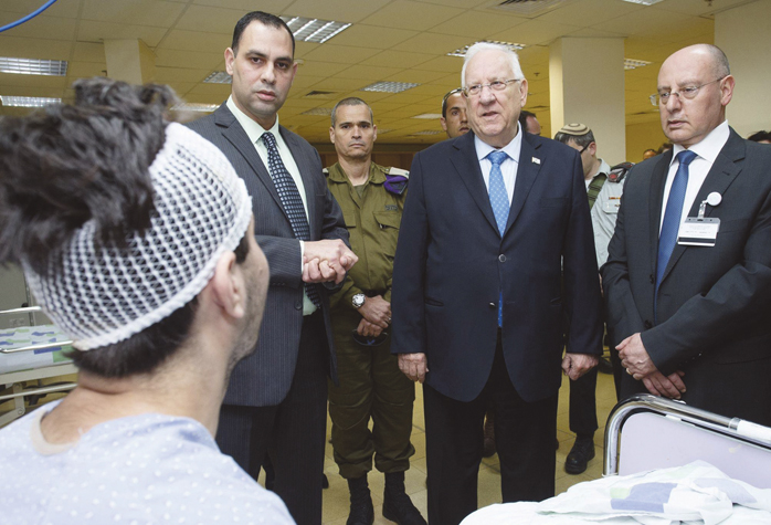 Israeli President Reuven Rivlin (2nd from R) speaks with a wounded Syrian at the Galilee Medical Center in Nahariya, April 9. To the right of Rivlin is Dr. Masad Barhoum, general director of Galilee Medical Center. Photo: Amos Ben-Gershom/GPO.