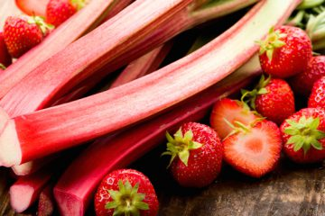 Fresh rhubarb and strawberries on a wooden underground