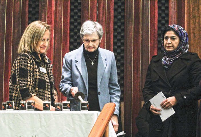Jewish Federation Dir. of External Relations Cheryl Carne (L) looks on as Women's Interfaith Discussion group organizers Sister Jeanette Buehler (Center) and Bushra Shahid light a candle at Temple Israel on Oct. 30 as part of the Dayton area Jewish community's program in memory of the victims of the Oct. 27 Pittsburgh synagogue massacre. Photo: Peter Wine.
