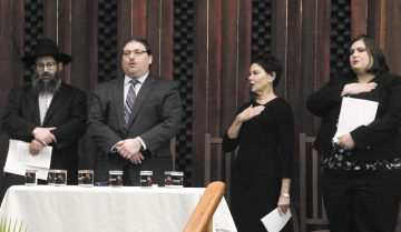 Standing for the U.S. National Anthem at Temple Israel on Oct. 30 during the Dayton area Jewish community's memorial for the victims of the Oct. 27 Pittsburgh synagogue massacre (L to R): Rabbi Nochum Mangel, Chabad of Greater Dayton; Rabbi Joshua Ginsberg, Beth Abraham Synagogue; Rabbi Judy Chessin, Temple Beth Or; and Rabbi Karen Bodney-Halasz, Temple Israel. Photo: Peter Wine.
