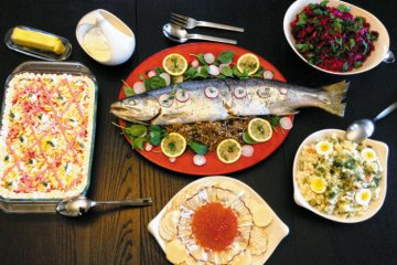 A New Year's Eve feast at the home of Masha Kisel and Sam Dorf. Center: Baked Salmon Stuffed and Served on Grechka (buckwheat). Clockwise from upper R: Vinegret (Beet Salad), Salat Olivier (Soviet Potato Salad), Salmon Caviar with crackers, and Shuba ('Herring Under A Fur Coat'). Photo: Masha I. Kisel.