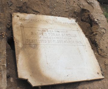 One of two stone markers at the site where Beth Abraham buried nine Torah scrolls destroyed in the 1913 flood. The markers were rediscovered in April. Photo: Marshall Weiss.